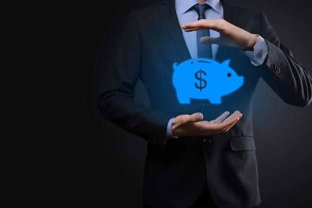 ビジネスマンは貯金箱のシンボルを保持します。ビジネスとお金の支出計画、および投資予算、ビジネス節約のお金の概念。節約または投資。