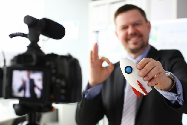 Бизнесмен держать ракету в руке крупным планом