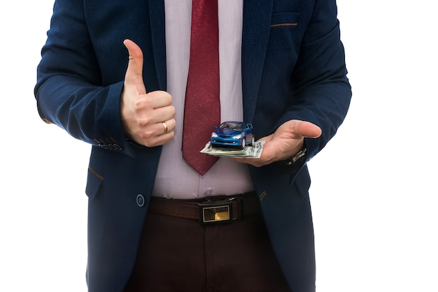 Businessman hold toy car and us money for sale or rent car isolated on white