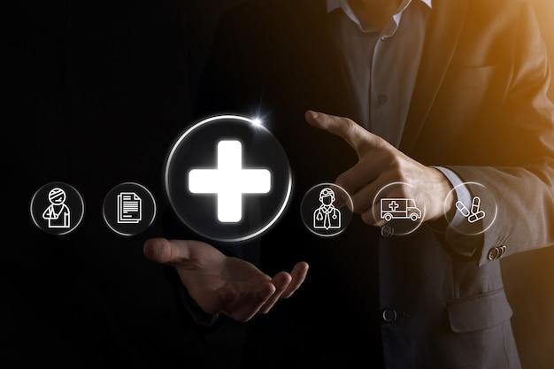 ビジネスマンは、仮想プラス医療ネットワーク接続アイコンを保持します。 covid-19パンデミックは人々の意識を高め、彼らのヘルスケアに注意を広めます。医師、文書、医療、救急車、患者のアイコン