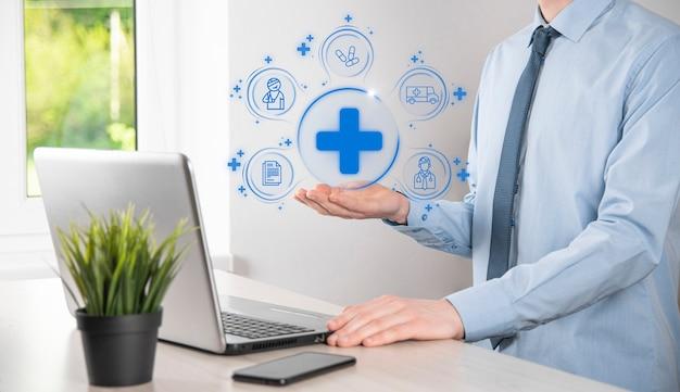 ビジネスマンは、仮想プラス医療ネットワーク接続アイコンを保持します。 covid-19パンデミックは人々の意識を高め、彼らのヘルスケアに注意を広めます。医師、文書、医療、救急車、患者のアイコン。