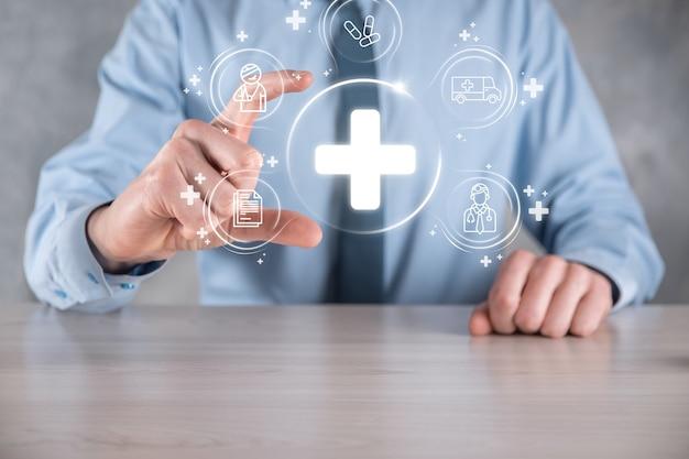 ビジネスマンは、仮想プラス医療ネットワーク接続アイコンを保持します。 covid-19 のパンデミックにより、人々の意識が高まり、医療への関心が高まります。医師、文書、医療、救急車、患者のアイコン。