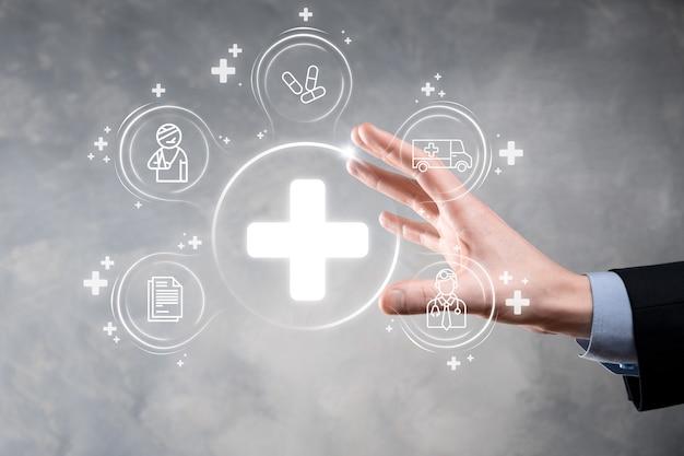 ビジネスマンは、仮想プラス医療ネットワーク接続アイコンを保持します。 covid-19 のパンデミックは、人々の意識を高め、医療への関心を広げます。医師、文書、医療、救急車、患者のアイコン。