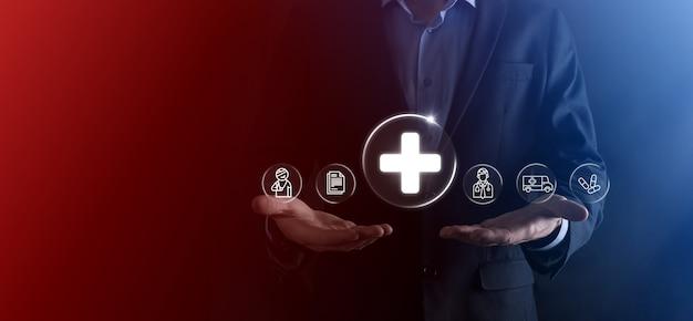 사업가는 가상 플러스 의료 네트워크 연결 아이콘을 보유하고 있습니다. 코비드-19 전염병은 사람들의 인식을 높이고 건강 관리에 대한 관심을 확산시킵니다. 의사, 문서, 의학, 구급차, 환자 아이콘. 프리미엄 사진