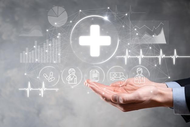 Бизнесмен держать виртуальные плюс значки подключения к медицинской сети. пандемия covid-19 повышает осведомленность людей и привлекает внимание к их медицинскому обслуживанию: врачу, документу, лекарству, машине скорой помощи, значку пациента.