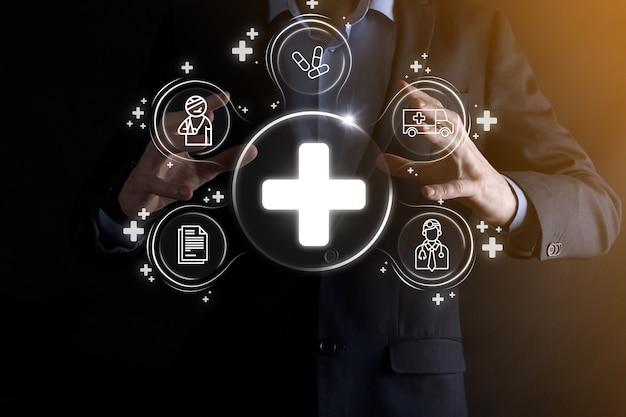 ビジネスマンは、仮想プラス医療ネットワーク接続アイコンを保持します。 covid-19パンデミックは人々の意識を高め、彼らのヘルスケアに注意を広めます。医師、文書、医療、救急車、患者のアイコン。 Premium写真