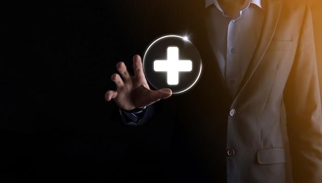 ビジネスマンは、仮想プラス医療ネットワーク接続アイコンを保持します。 covid-19パンデミックは、人々の意識を高め、ヘルスケアへの注目を広めます。 Premium写真