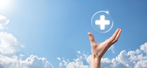 사업가는 가상 플러스 의료 네트워크 연결 아이콘을 보유하고 있습니다. covid-19 전염병은 사람들의 인식을 높이고 건강 관리에 대한 관심을 확산시킵니다.