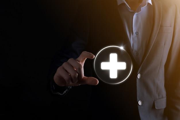 ビジネスマンは、仮想プラス医療ネットワーク接続アイコンを保持します。 covid-19パンデミックは、人々の意識を高め、ヘルスケアへの注目を広めます。