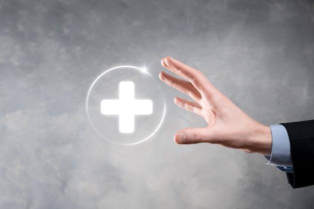 ビジネスマンは、仮想プラス医療ネットワーク接続アイコンを保持します。 covid-19 のパンデミックにより、人々の意識が高まり、医療への注目が広がります。