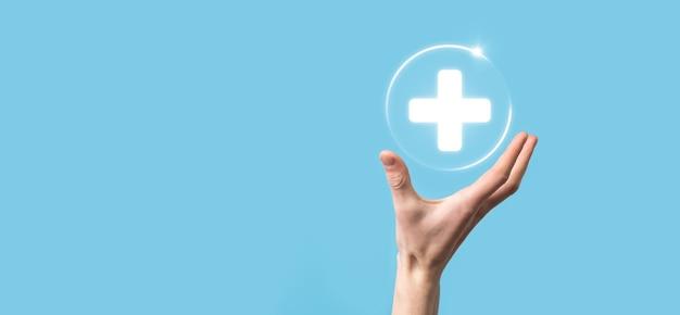 Бизнесмен держать виртуальные плюс значки подключения к медицинской сети. пандемия covid-19 способствует повышению осведомленности людей и привлечению внимания к их медицинскому обслуживанию.