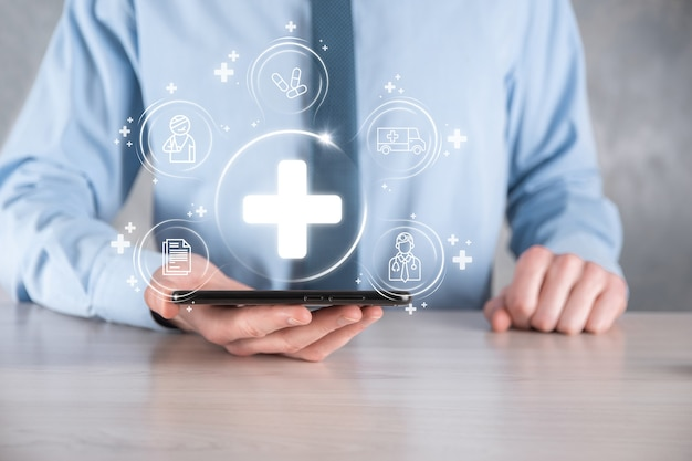 ビジネスマンは、仮想プラス医療ネットワーク接続アイコンを保持します。 covid-19パンデミックは人々を開発します
