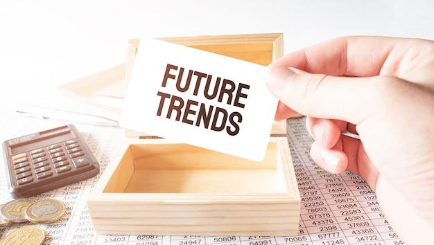 Бизнесмен держать белую карточку с текстом будущих тенденций