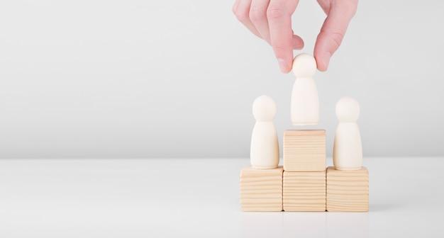Бизнесмен держать деревянного человека, представляющего лидера, увеличивает успех, стоя на пьедестале.