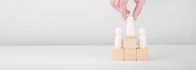 ビジネスマンは台座の上に立って成功をステップアップするリーダーを表す木製の男を保持します