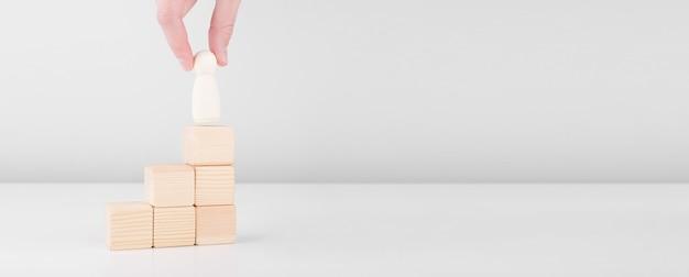 Бизнесмен удерживает деревянного человека, представляющего лидера, увеличивает успех