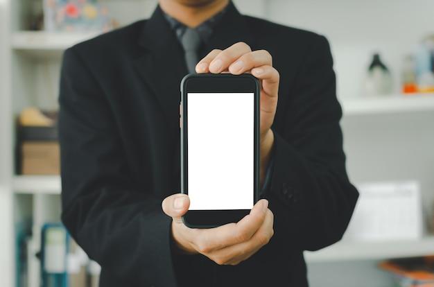 Бизнесмен, держащий пустой белый смартфон с сенсорным экраном. используется для размещения текста или информации для рекламы новостей или продажи товаров в интернете. концепция маркетинга бизнеса