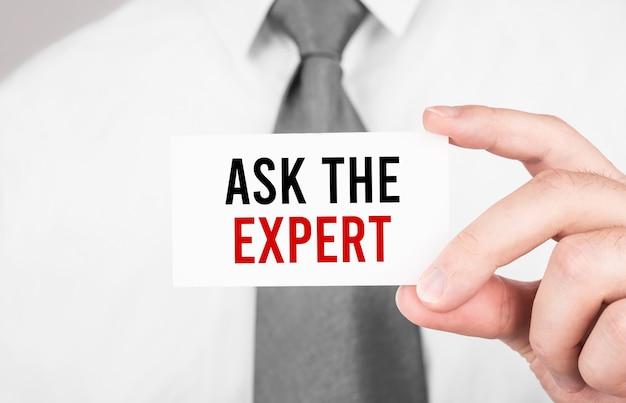 Бизнесмен, держа карточку с текстом спросите эксперта, бизнес-концепция