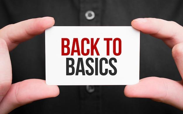 基本、ビジネスコンセプトに戻るテキストでカードを保持しているビジネスマン
