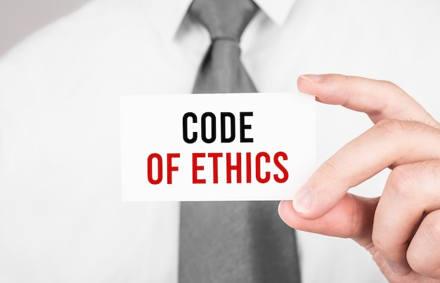 倫理規定、ビジネスコンセプトのテキストでカードを保持しているビジネスマン