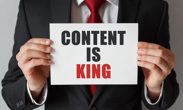 テキストコンテンツのカードを持っているビジネスマンは王様です