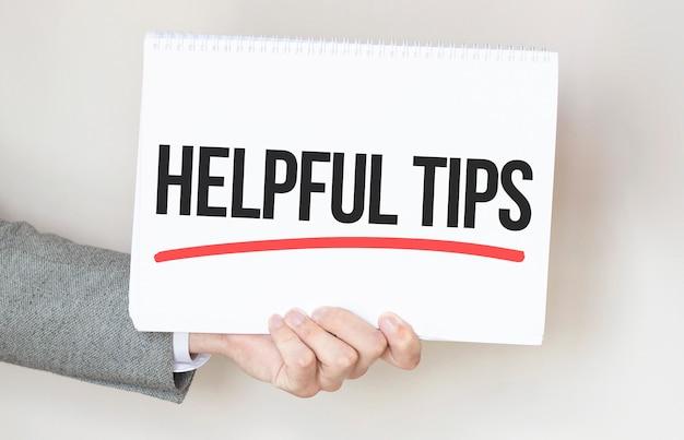 テキストとカードを保持しているビジネスマン役立つヒント