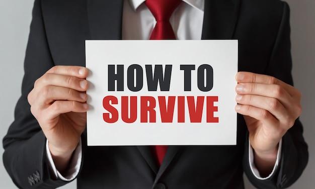 Бизнесмен держит карточку с текстом, как выжить