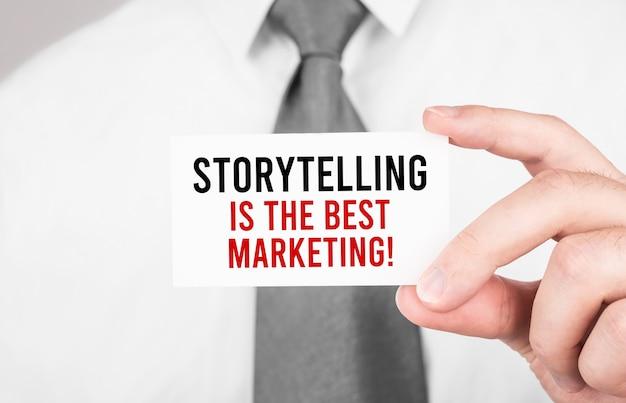 Бизнесмен, держащий карточку с текстом рассказывание историй - лучший маркетинг, бизнес-концепция