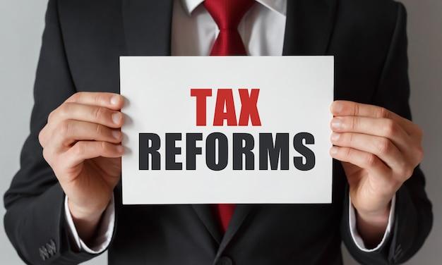 Бизнесмен, держа карту с текстом налоговых реформ