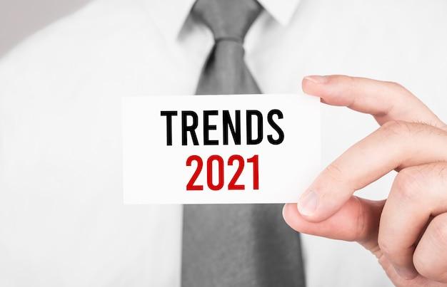 テキストtrends2021、ビジネスコンセプトのカードを保持しているビジネスマン
