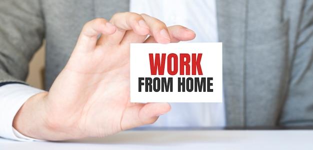テキスト「在宅勤務」のカードを持っているビジネスマン。ビジネスコンセプト