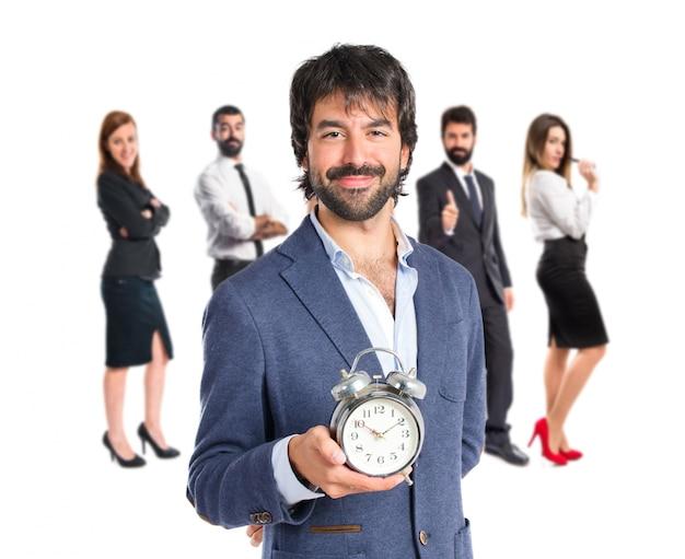 흰색 배경 위에 시계를 들고 사업