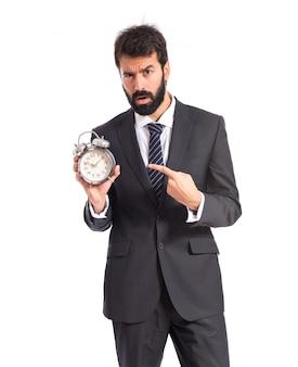 白い背景の上に時計を持っているビジネスマン