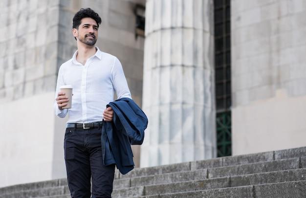 屋外で仕事に行く途中でコーヒーを持っているビジネスマン