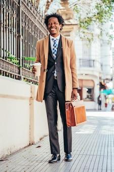 거리에서 야외에서 일하기 위해 그의 길에 걷는 동안 커피 한 잔을 들고 사업가.