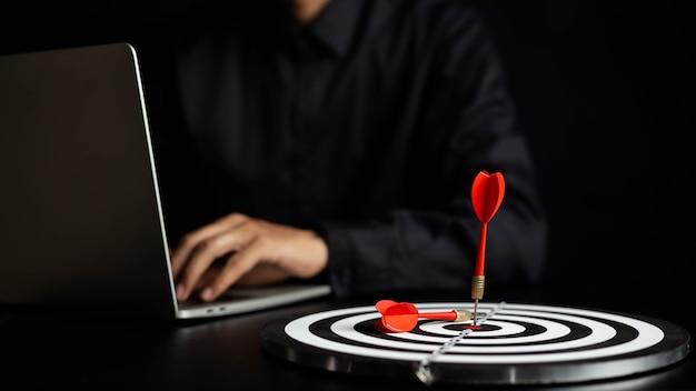 Бизнесмен, держащий дартс, направленный на концепцию бизнес-цели целевой центр -
