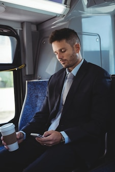 Бизнесмен, держа одноразовые чашки кофе и с помощью мобильного телефона