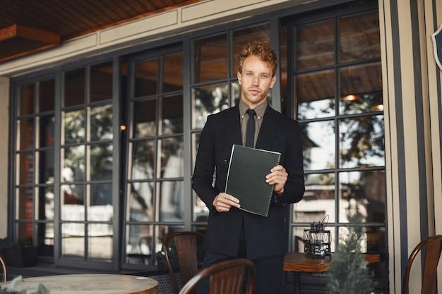그의 손에 폴더를 들고 사업가입니다. 양복 서 입고 잘 생긴 자신감 사업가입니다.