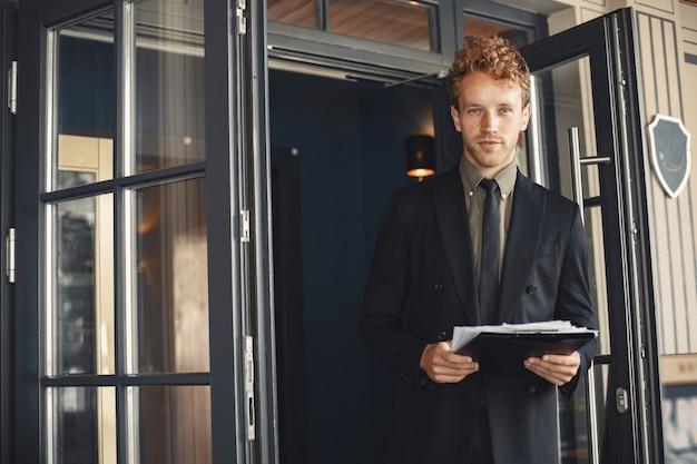 彼の手でフォルダーを保持しているビジネスマン。立っているスーツを着てハンサムな自信を持ってビジネスマン。