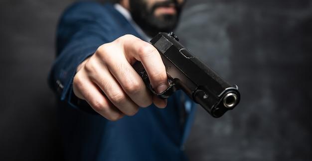 Бизнесмен, держащий пистолет на темной поверхности