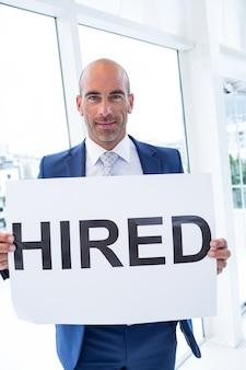 雇われたサインを持っている実業家