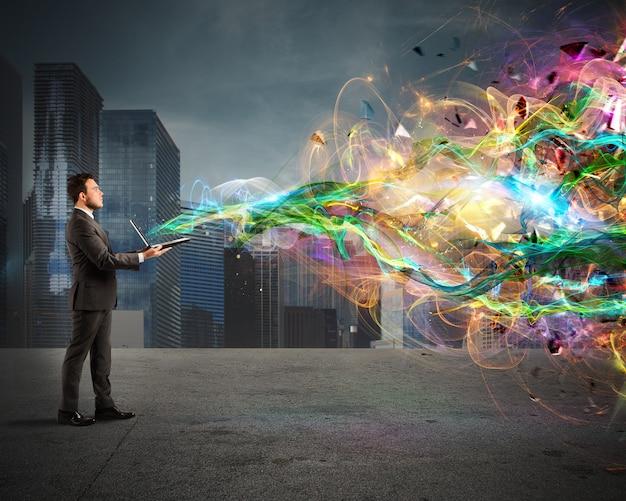 華麗な照明効果を持つラップトップを保持しているビジネスマン。創造的で現代的な技術の概念