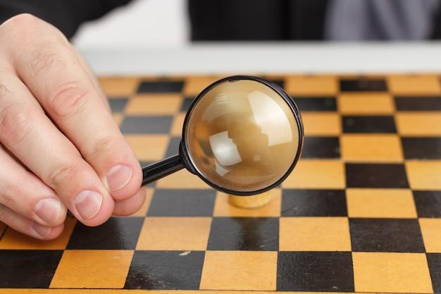 Бизнесмен, держащий увеличительное стекло, помещен на шахматную доску.