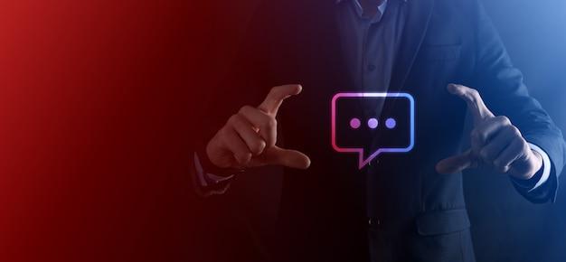 メッセージアイコン、バブルトーク通知サインを手に持っているビジネスマン。チャットアイコン、smsアイコン、コメントアイコン、吹き出し