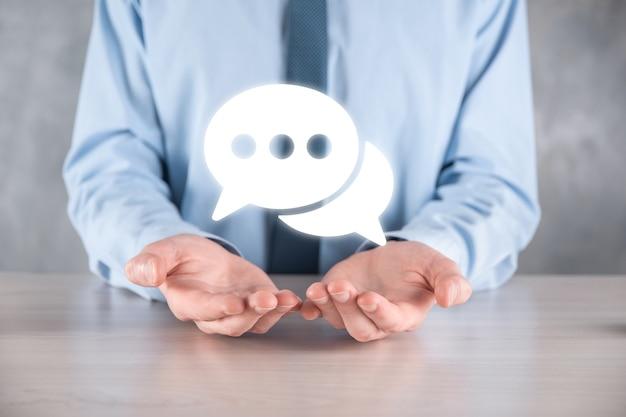 Бизнесмен, держа значок сообщения, знак уведомления пузырь разговора в его руках. значок чата, значок смс, значок комментариев, пузыри речи