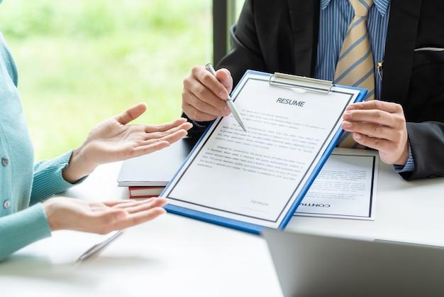 求職者がオフィスで説明するために履歴書を指すペンを持っているビジネスマン。