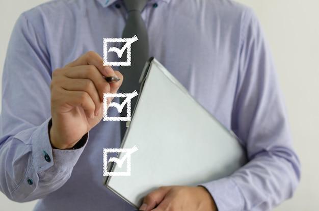 가상 화면의 사각형에 확인 표시가 있는 펜을 들고 있는 사업가