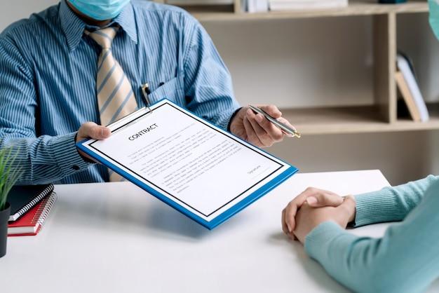 オフィスで働く契約書に署名するために顧客に渡された契約書とペンを持っているビジネスマン。