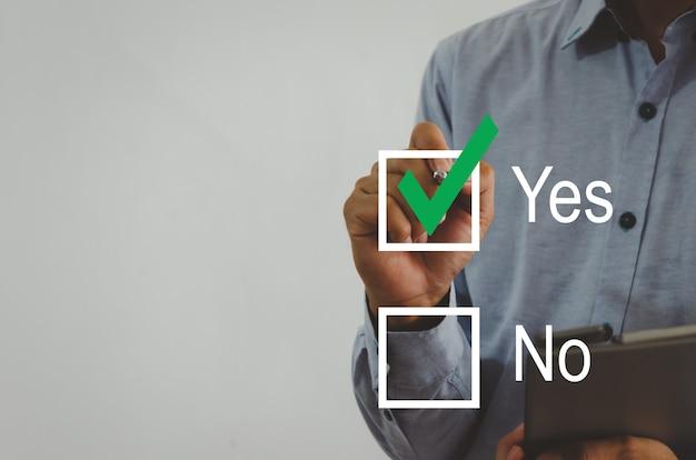 가상 화면의 사각형에 녹색 확인 표시가 있는 펜을 들고 있는 사업가