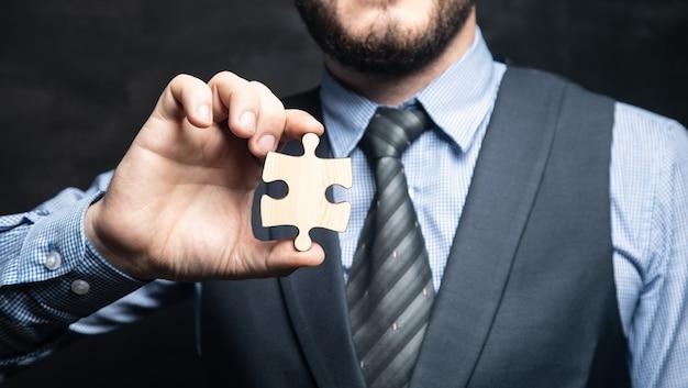 Бизнесмен, держа в руке кусок головоломки на черной поверхности